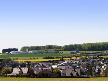 Auf dem Bild befindet sich die Ortsansicht von Blankenrath und rings herum Felder und Bäume.