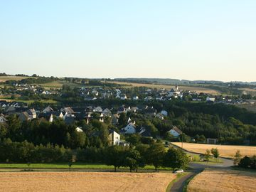 Das Bild zeigt eine Ortsansich von Mittelstrimmig. Im Vordergrund erkennt man einen Weg der durch den Ort führt und im HIntergrunden befinden sich Felder.