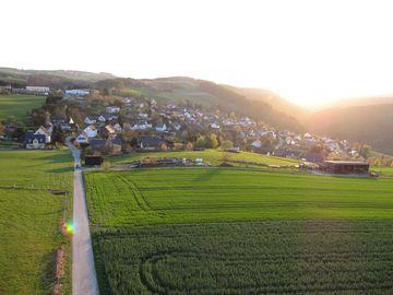 Auf dem Bild befindet sich im Vordergrund Wiese und im Hintergrund der Ort Altlay.