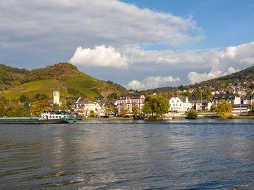 Das Bild ist von dem Fluss aus aufgenommen. Auf dem Bild befindet sich die Mosel, ein Schiff und der Ort Bullay.